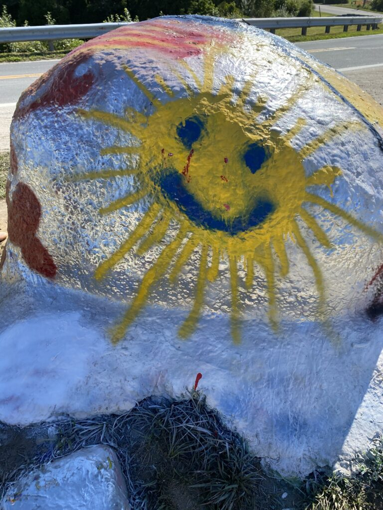 large boulder painted with a bright yellow smiley face in the shape of the sun