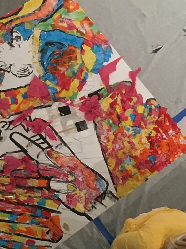 overhead photo of table of colorful pieces of collage paper